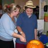 student & instructor carving a pumpkin
