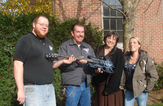 Volunteers hand the guitar over to The Birchtree Center staff